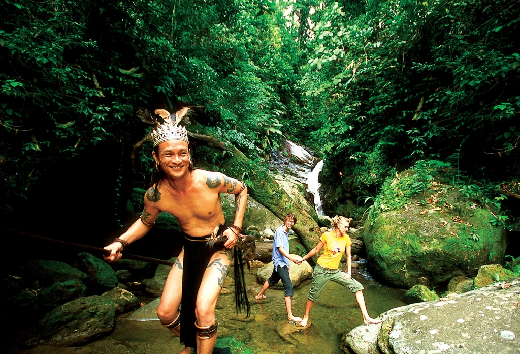 Native guide with tourists in Sarawak Jungle